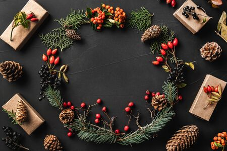 Crown of Christmas tree branches, pine cones, berries, walnuts, gifts, on black stone background. Xmas and Happy New Year theme. Flat lay, top view