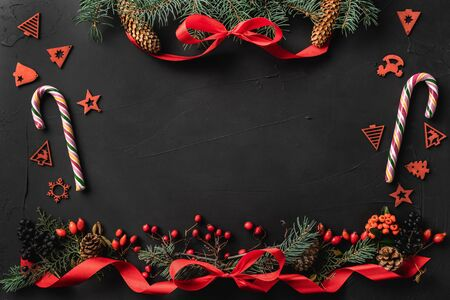 Christmas composition of fir branches, pine cones, berries, gifts and red slack, on black stone background. Candy and toys. Xmas and Happy New Year theme. Flat lay, top view Foto de archivo