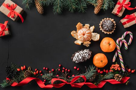 Christmas composition of fir branches, pine cones, berries, gifts and red slack, on black stone background. Candy, sweets, mandarins and many gifts. Xmas and Happy New Year theme. Flat lay, top view