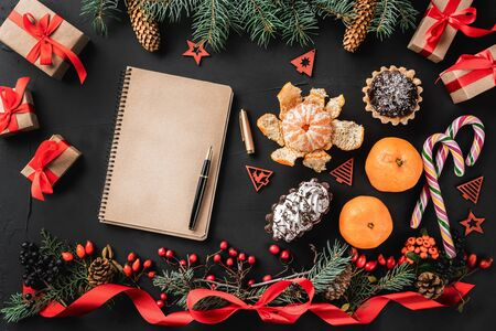 Christmas composition of fir branches, pine cones, berries, gifts and red slack, on black stone background. Candy, sweets, mandarins, gifts. Textbook. Xmas and Happy New Year theme. Flat lay, top view