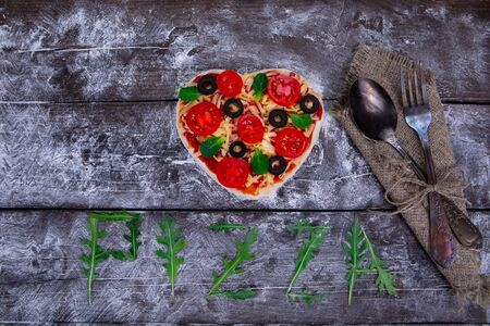 Preparation of heart-shaped pizza from ingredients such as dough, tomatoes, olives, basil, cheese, on a dark wooden board and pressed with flour next to the napkin, spoon and fork. Top view. Stock fotó