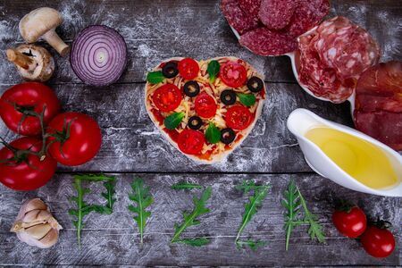Preparation of heart-shaped pizza from ingredients such as dough, tomatoes, ketchup, olives, basil, lemon juice, sausage, mushrooms onion, garlic and cheese on a dark wooden board. Top view. Stock fotó