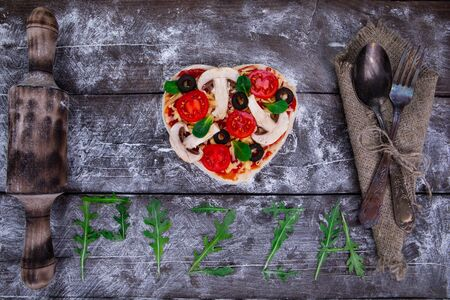 Preparation of heart-shaped pizza from ingredients such as dough, tomatoes, olives, basil, cheese, rooling pinon a dark wooden board and pressed with flour next to the napkin, spoon and fork. Top view Stock fotó