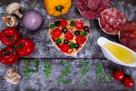 Heart shaped pizza ingredients. The name of the pizza is written in arugula. Stock fotó