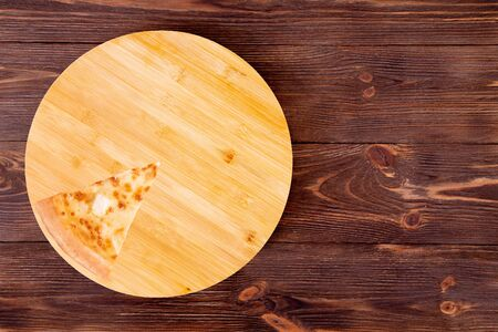 A slice of pizza five cheeses on bamboo bottom, on wooden table, top view, space for text