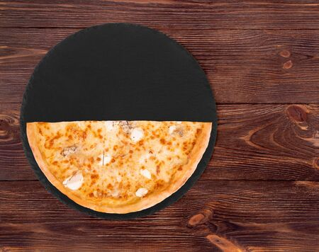 Half of pizza five cheeses on slate bottom, on wooden table, top view, space for text