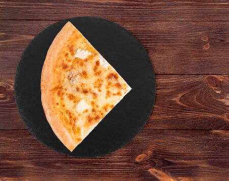 A slice of pizza five cheeses on slate bottom, on wooden table, top view, space for text Stock Photo