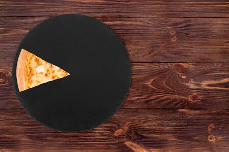 A slice of pizza five cheeses on slate bottom, on wooden table, top view, space for text