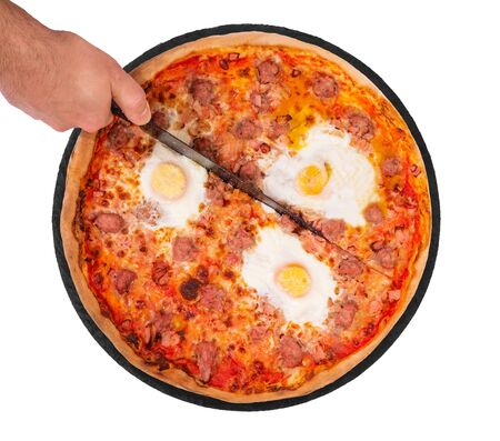 The chef cuts the pizza with a kitchen knife. Pizza with beef sausages, eggs and bacon on the slate plate, isolate on white background, top view