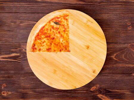 Quarter of pizza with mozzarella, bocconcini and basil leaves or pizza margherita on round wood plate which is on wooden rustic background, top view Stock Photo