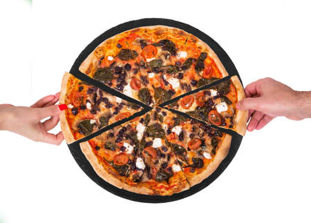 People hands taking slices of pizza with cherry tomatoes, spinach, mozzarella, feta, kalamata olive and mushrooms from the slate black round plate, isolated on white background