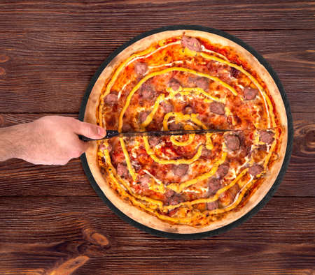 Man cuts the salsiccia pizza with a kitchen knife. Delicious pizza with beef sausages, mozzarella, various sauces and marinated red onions on slate platter which is on wooden table, top view