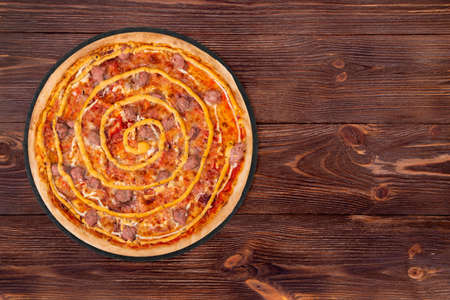 Delicious salsiccia pizza with beef sausages, mozzarella, various sauces and marinated red onions on round slate platter which is on the wooden table, top view and copy space