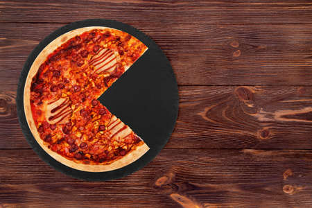 Delicious BBQ pizza with ham, bbq sauce, bacon and salami, without a quarter on a black slate platter which is on wooden table, top view and copy space