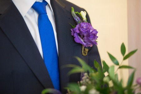 boutonniere: Blue beautiful boutonniere on black grooms suit