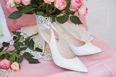church bells: White Wedding shoes and pink little roses Stock Photo