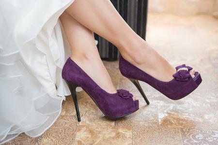 morado: Zapatos de la boda púrpuras en los pies de la novia