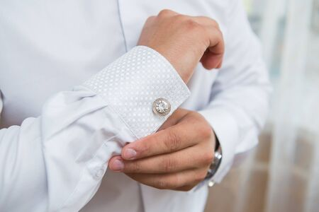 cuff links: close up of a hand man how wears white shirt and cufflink