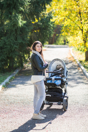 middle eastern woman: Middle eastern woman with stroller going for a walk in a park during lovely autumn afternoon