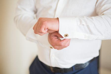wrist cuffs: close up of a hand man how wears white shirt and cufflink