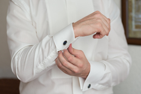 suit  cuff: close up of a hand man how wears white shirt and cufflink