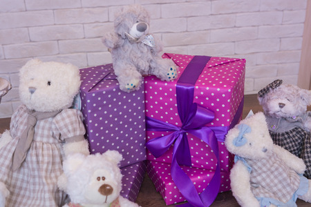 favorite colour: Seated teddy bear with gift boxes, over a light background Stock Photo