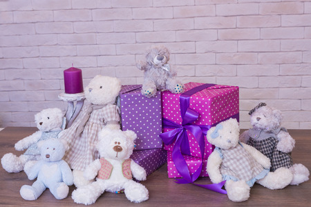 seated: Seated teddy bear with gift boxes, over a light background Stock Photo