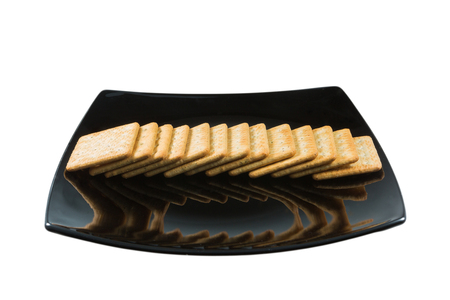 pileup: Cracker in black dish isolated on white