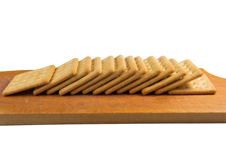 pileup: Cracker in a wooden cutting board isolated on white Stock Photo