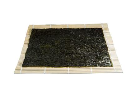 nori: Kombu and kim nori on bamboo mat over white background