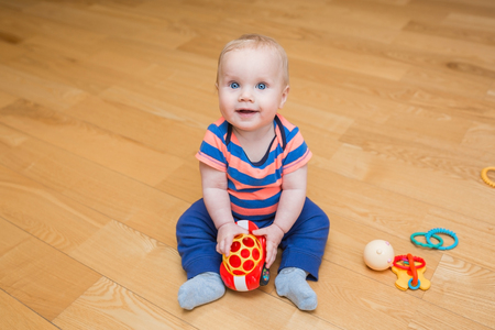 kids toys: baby boy playing with his toys indoors at home Stock Photo