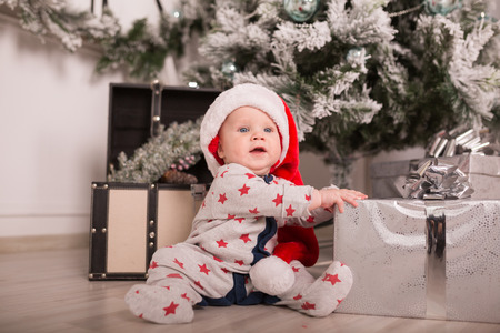 christmas costume: Beautiful little baby celebrates Christmas. New Years holidays. Baby in a Christmas costume with gift
