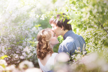 Love couple standing among blooming apple tree, spring