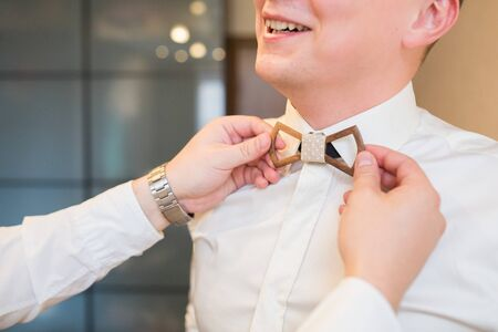 man's suit: Mans hands touches Wooden  bow-tie on a suit Stock Photo
