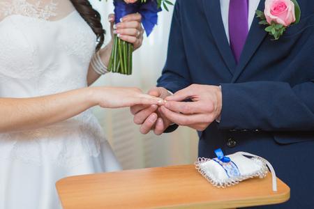 fingers put together: Groom putting gold ring on brides finger