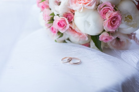 結婚式: 2 つの結婚指輪と春の花。結婚式のコンセプト。