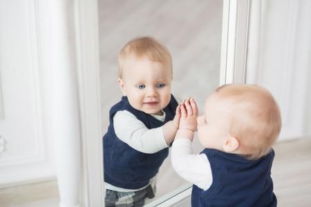 Diez meses bebé niño de pie ante el espejo y jugar con él