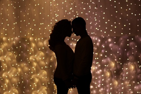 Romantic couple kissing silhouette on the light background