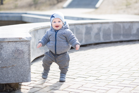 one child: A one year old boy taking some of his first steps outdoors in spring park.