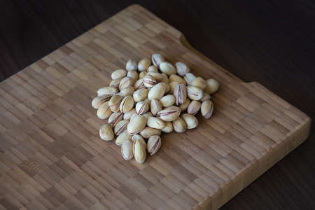 mistic: Pistachios on wooden background. Dark and moody style. Magic moon and mistic light Stock Photo