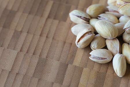 mistic: Pistachios on wooden background. Dark and moody style. Magic moon and mistic light. Bamboo and wooden board background with free text space. Stock Photo