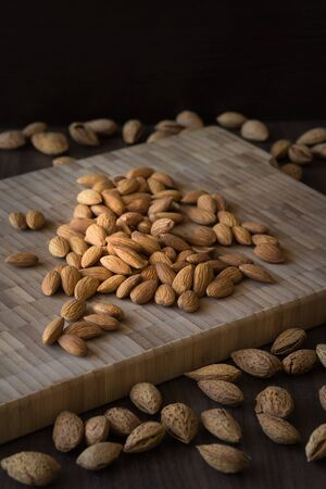 mistic: Almonds on wooden background. Peeled and unpeeled nuts on dark table. Dark and moody style. Magic moon and mistic light