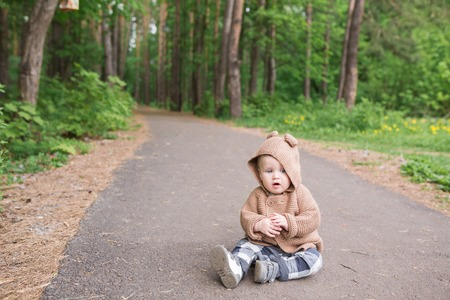toddler walking: A one year old baby boy sitting outdoors in spring park. Cute toddler walking in the green forest in summer Stock Photo