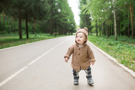 one year old: A one year old baby boy taking some of his first steps outdoors in spring park. Cute toddler walking in the green forest in summer Stock Photo