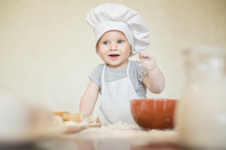Prodigy: The little boy in a suit of the cook sculpts dough. Baby scullion make dinner in chef suit. Cooking concept