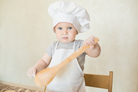 a little dinner: The little boy in a suit of the cook sculpts dough. Baby make dinner in chef suit
