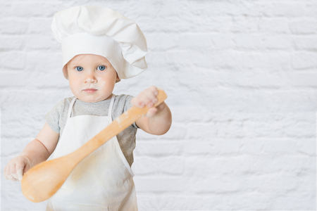 a little dinner: The little boy in a suit of the cook sculpts dough. Baby make dinner in chef suit. Cooking concept with free text space - copy space