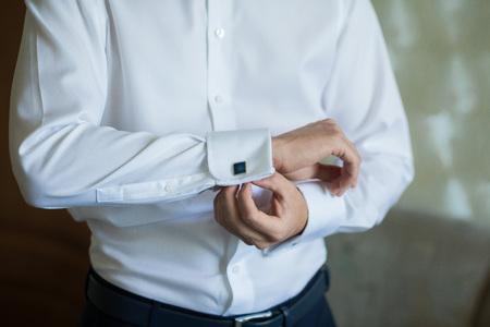 cufflink: close up of a hand man wears white shirt and cufflink
