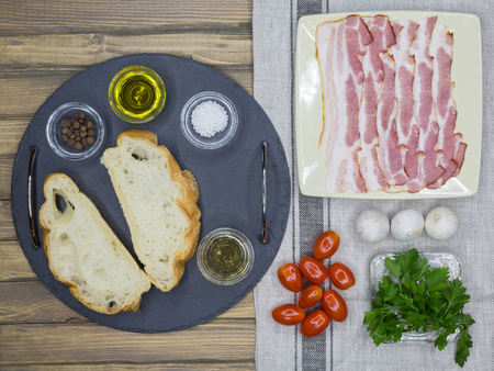 collation: Top view of ingredients for Bruschetta with bacon, tomatoes, herbs and oil on toasted garlic cheese bread ciabatta