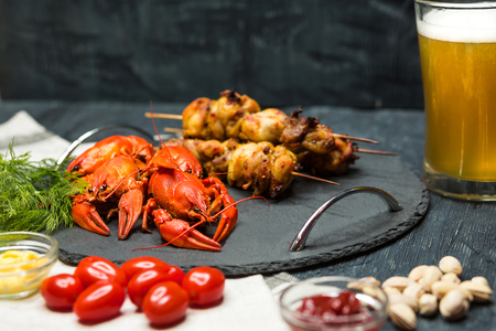 Tasty boiled crayfishes, barbecueand and beer on wooden table with vegetables and sauce. snacks for drinks Concept Stock Photo